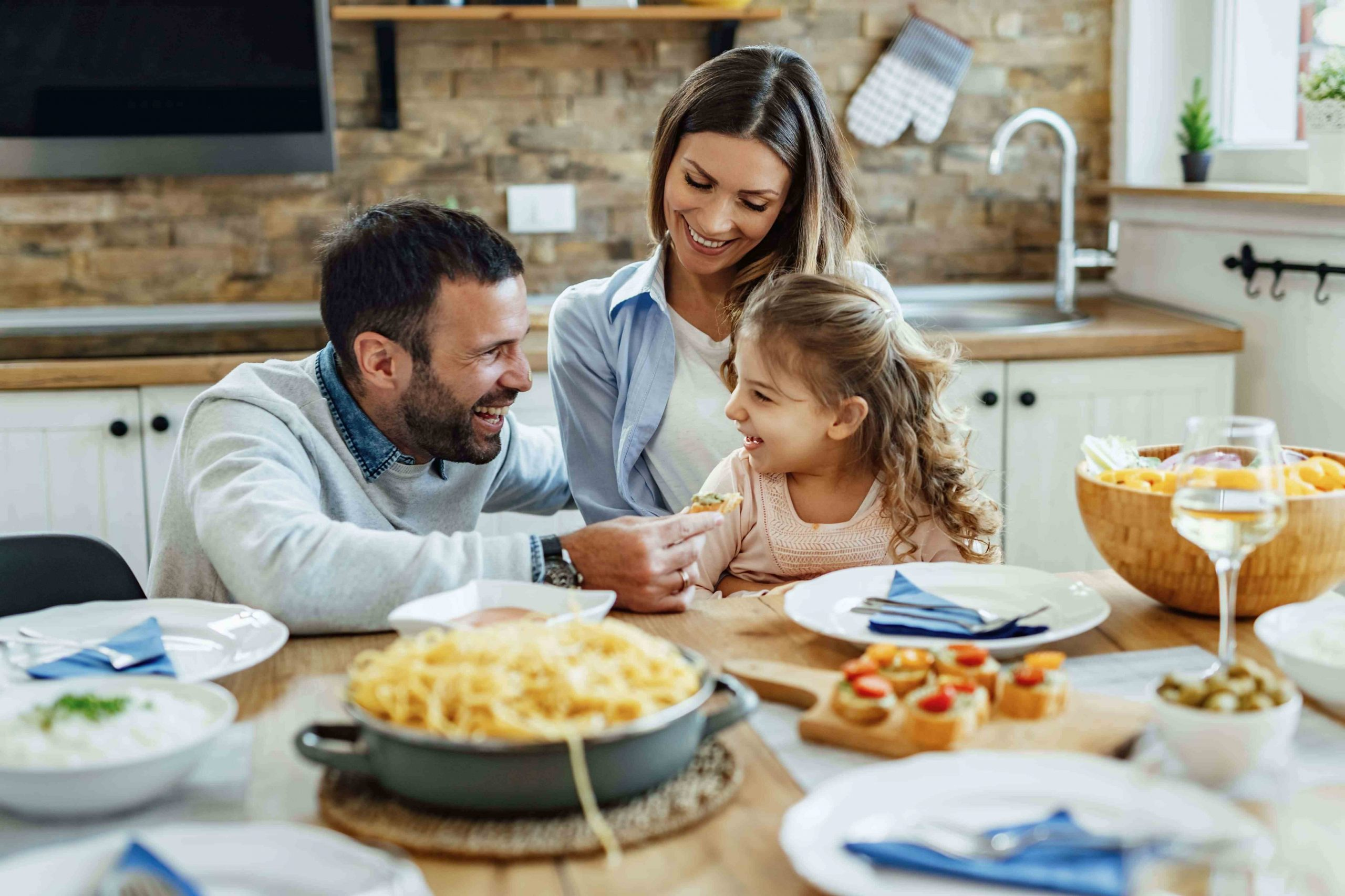 Happy parents and their small daughter having fun during family lunch at home.