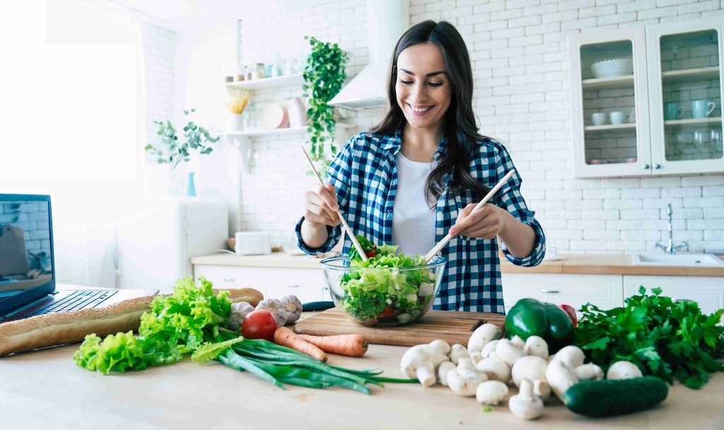 Girl preparing salad in a bright kitchen